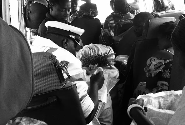 Minibus in Tanzania flagged by a cope (in white hat) due to overloading.