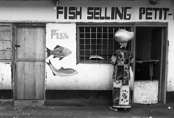 Woman waiting to be served at a fish joint in Dzaleka Refugee Camp in Malawi.