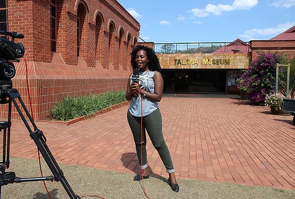 NomadTV presenter in front of the Talana Museum.