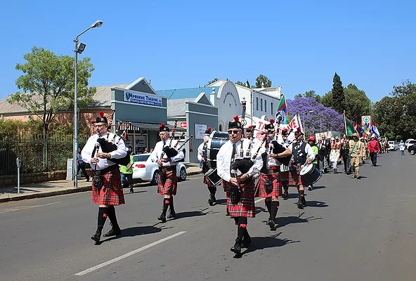 Piping the lament as officials parade through the town of Dundee led by Pipe Band, re-enactors, cultural groups, cars and motor cycles to start this year's Talana live event.