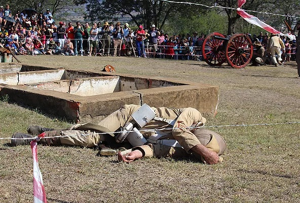 A dead Boer soldier during the re-enactment of the battle of Talana. Participating crowd watch with keen interest.