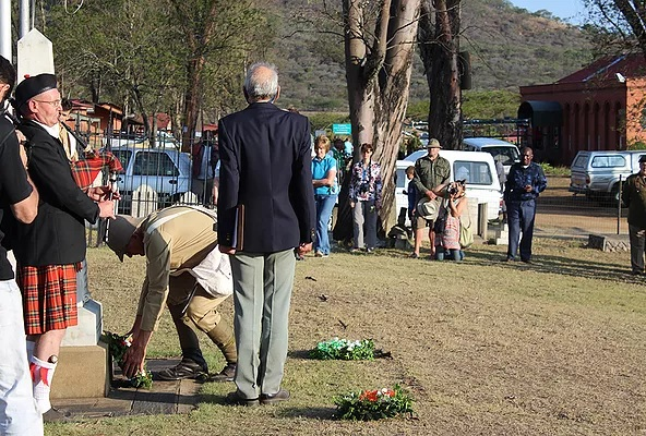 Piping the lament and lowering of flags at the Talana cemetery as a Boer soldier places red roses in honour of the fallen heroes of the Talana Battle.