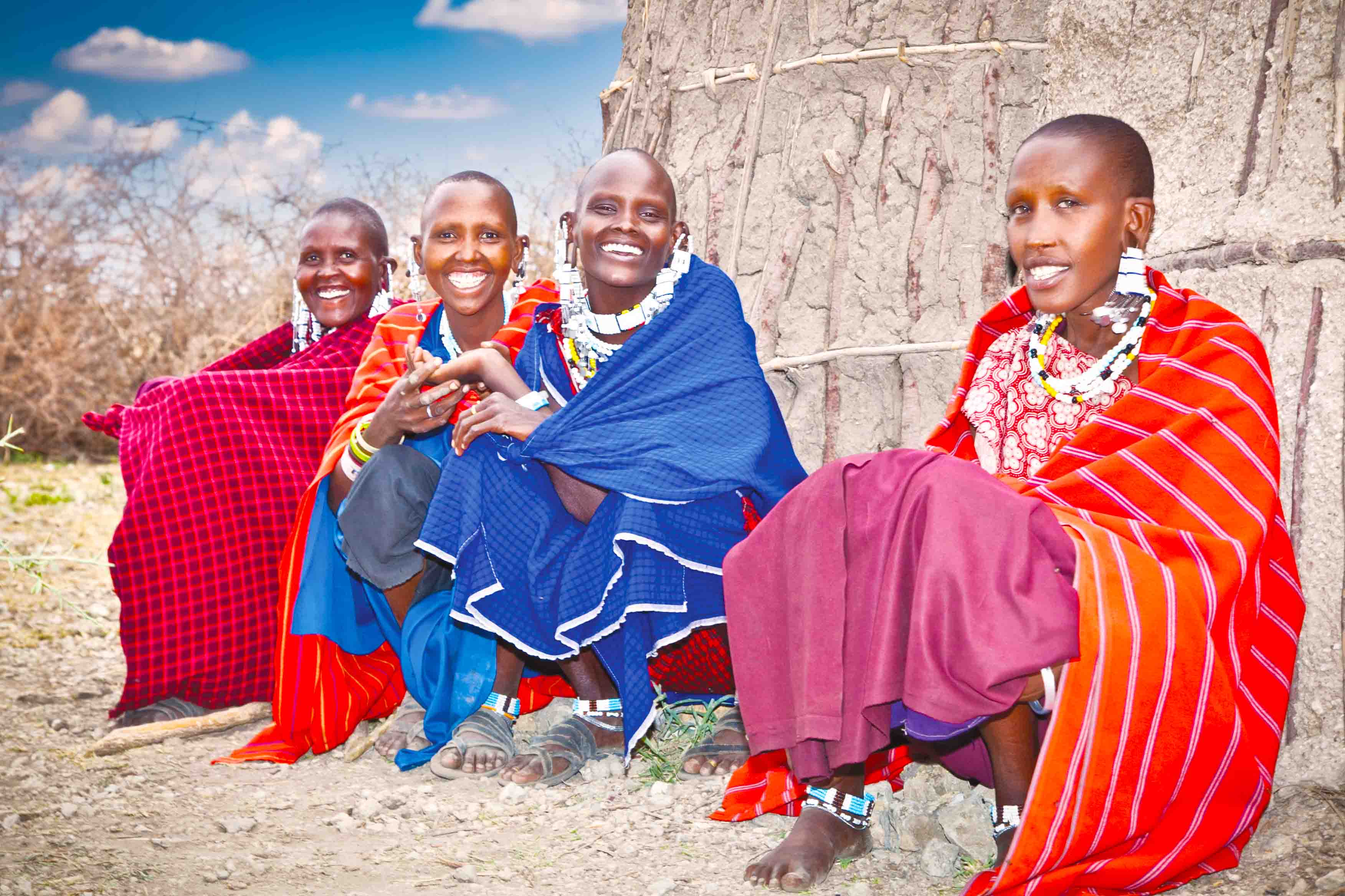 Women outside the hut. The women had woken the girls up in the wee hours of the morning to adorn them with the traditional Maasai jewels and mark their heads with okra.